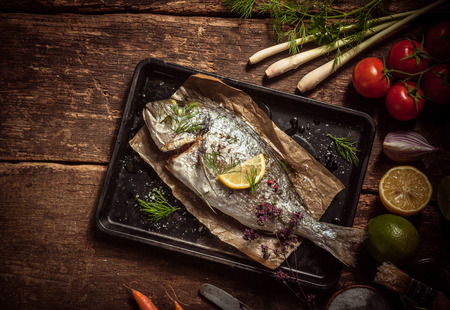 grilled fish: Fish Meat on a Black Tray with Herbs and Spices on Top of a Rustic Wooden Table with Organic Veggies. Captured in High Angle View.