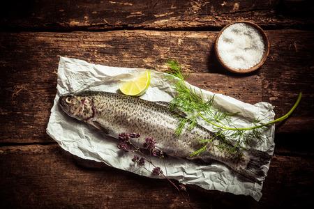 truchas: Cierre de pescados sin procesar de la carne en un Libro con Hierbas y Especias en encima de una mesa rústica con sal y rojos Tomates en el lateral. Capturado en Vista elevada.