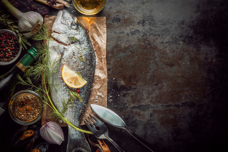 half fish: Raw Fish on Brown Paper Surrounded by Various Spices and Seasonings with Copy Space Stock Photo