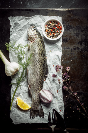 Overhead View of Raw Fish on White Paper Surrounded by Various Spices and Seasonings on Dark Counter Top photo