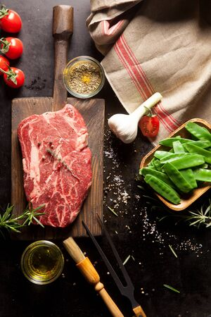 hand towel: Still Life of Raw Ingredients for Preparing Dinner Meal - Raw Steak on Cutting Board, Snow Peas in Wooden Dish, Garlic Bulb and Various Herbs and Spices and Hand Towel Stock Photo