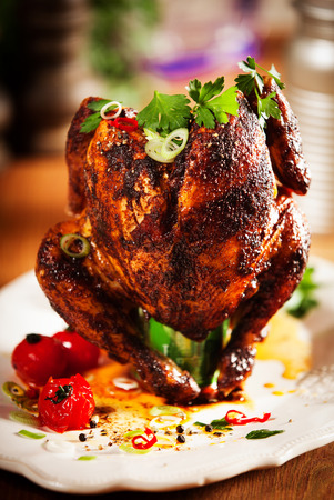 Close up Gourmet Appetizing Roast Whole Chicken on a White Plate with Herbs and Spices Stock Photo