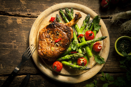 lamb chop: Close up Gourmet Grilled veal loin Steak Meat with Asparagus and Cherry Tomatoes on a Wooden Cutting Board, Served on Top of a Rustic Table. Captured in High Angle View.