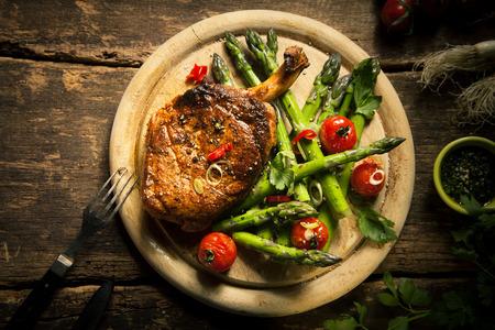 liggande: Närbild Gourmet Grillad kalv ländryggen biff kött med sparris och körsbärstomater på en trä skärbräda, serveras på toppen av en Rustik tabell. Fångas i Hög vinkel.