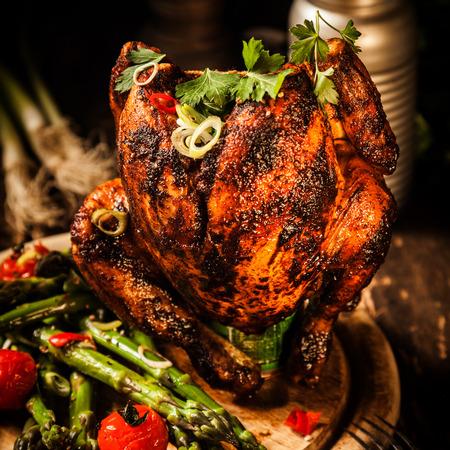 pollo rostizado: Cierre de Gourmet asado entero Beer Can pollo con esp�rragos, tomates cherry, la hierba y especias, servido en la cima de una tabla de madera.