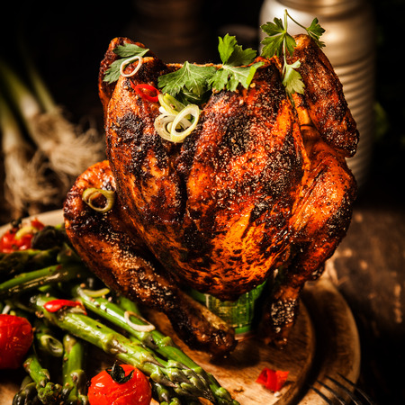 spicy: Close up Gourmet Roast Whole Beer Can Chicken With Asparagus, Cherry Tomatoes, Herb and Spices, Served on Top of a Wooden Table. Stock Photo