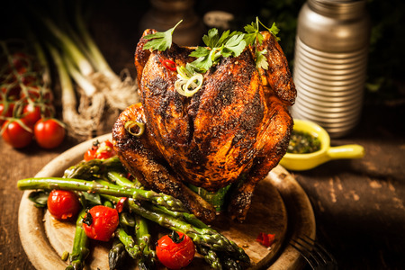 Gourmet Grilled Whole Beer Can Chicken on Top of Round Wooden Board with Cooked Asparagus, Cherry Tomatoes and Herbs for Dinner.