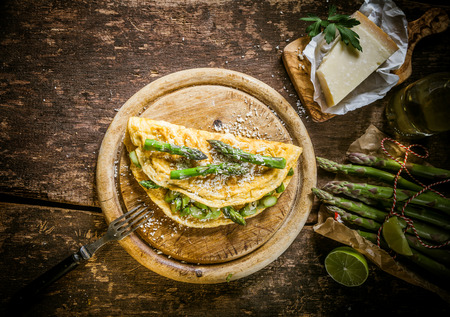 omelette: Gourmet Tasty Egg Omelette with Asparagus and Cheese on Top of Wooden Round Cutting Board, Served on Rustic Wooden Table, Captured in High Angle View. Stock Photo
