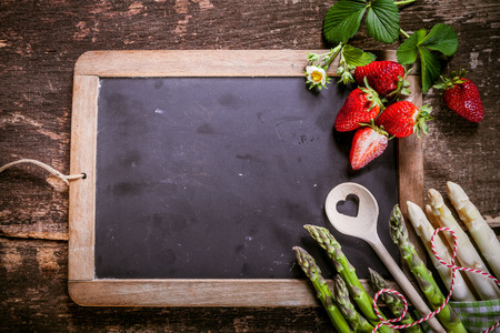 emphasizing: Small Empty Black Chalkboard with Fresh Asparagus and Strawberries on the Edge, Placed on Rustic Table, Emphasizing Copy Space. Stock Photo
