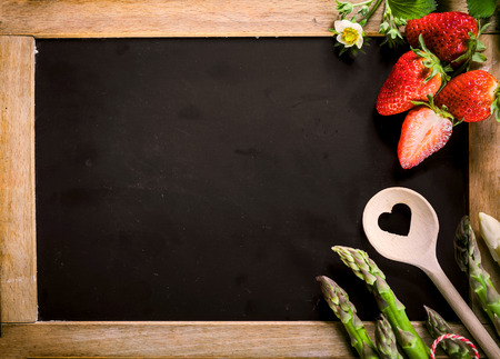 Close up Empty Black Chalkboard with Asparagus, Berries and Ladle on the Right Edge, Emphasizing Copy Space for Texts.