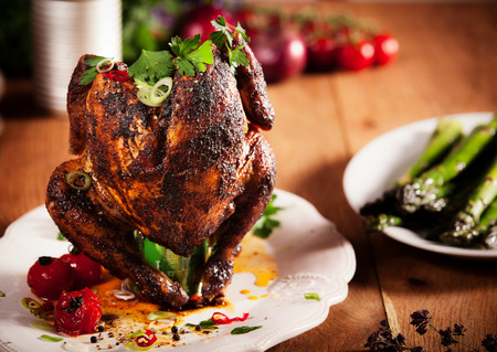 Close up Gourmet Grilled Whole beer can Chicken on a White Plate with Herbs and Spices, Served on Top of Wooden Kitchen Table.