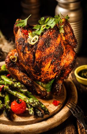 pollo rostizado: Cierre de Dish Gourmet sabrosa parrilla entera Beer Can carne de pollo principal en madera tabla de cortar redonda con espárragos, tomates cherry y hierbas.