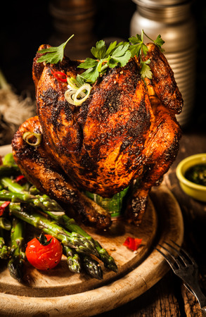 Close up Gourmet Tasty Grilled Whole Beer Can Chicken Meat Main Dish on Wooden Round Cutting Board with Asparagus, Cherry Tomatoes and Herbs. photo