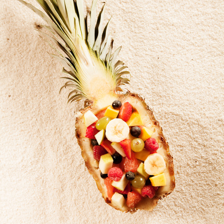 fruity salad: Fresh exotic tropical fruit salad served in a halved pineapple on a textured white background in summer sunshine, viewed from overhead