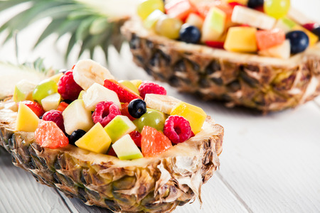 fruity salad: Colorful Fresh Tropical Fruit Salad in Pineapple Boat on Top of a Wooden White Table. Captured in Macro. Stock Photo