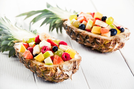 mouth watering: Close up Gourmet Mouth Watering Fresh Tropical Fruit Salads in Pineapple Boats for Two Served on a White Table.