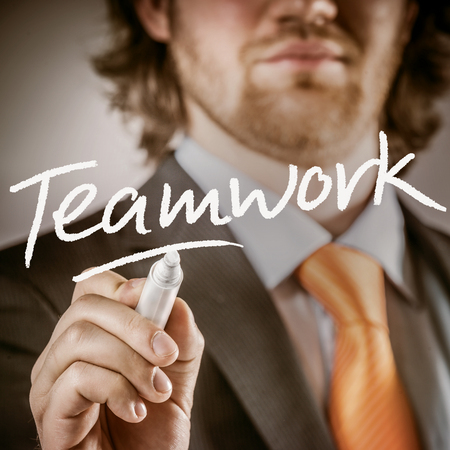 teamworking: Close up Bearded Businessman Writing on a Glass Board Using a Marker for Teamwork Concept.