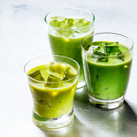 Three Drinking Glasses Filled with Healthy Green Smoothie Shake Made from Avocado and Kiwi, Cooled with Ice on Shiny Silver Metal Surface photo