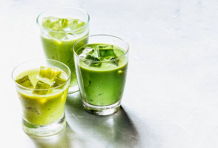 Three Drinking Glasses Filled with Healthy Green Smoothie Shake Made from Avocado and Kiwi, Cooled with Ice on Shiny Silver Metal Surface with Copy Space photo