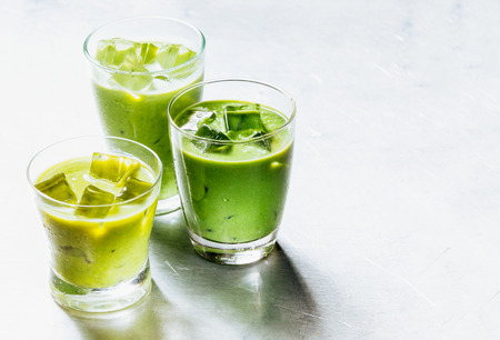 fruity salad: Three Drinking Glasses Filled with Healthy Green Smoothie Shake Made from Avocado and Kiwi, Cooled with Ice on Shiny Silver Metal Surface with Copy Space Stock Photo