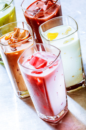 chilled: Variety of Ice Chilled Healthy Smoothie Shakes in Tall Glasses on Metal Surface