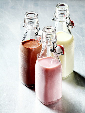 flavoured: Still Life of Healthy Blended Smoothie Shakes in Three Glass Bottles with Open Tops on Shiny Metal Surface