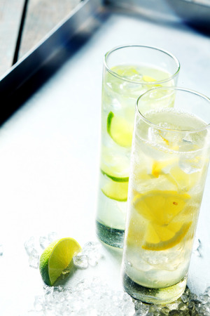 quench: Refreshing ice cold pure water flavoured with tangy citrus slices served in tall glasses to quench a summer thirst Stock Photo