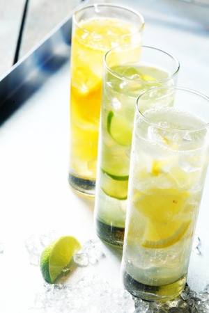 quenching: Tall glasses of iced citrus drinks for summer served on ice with fresh sliced fruit for a quenching beverage