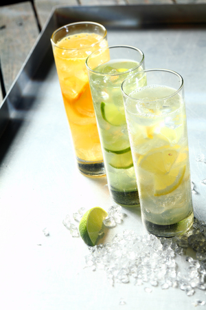 tangy: Three refreshing tangy citrus summer cocktails served in tall glasses flavoured with lemon, lime and orange and chilled on ice, high angle view in a receding row