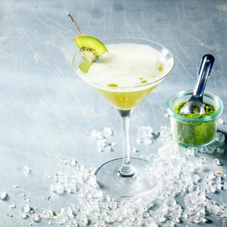 copa martini: Cóctel de té verde Matcha sirve en una copa de martini cónica con guarnición de kiwi y hielo picado, vista de ángulo alto con copyspace con un tarro de polvo matcha junto