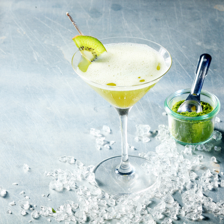cocktail drinks: Matcha green tea cocktail served in a conical martini glass with kiwifruit garnish and crushed ice, high angle view with copyspace with a jar of matcha powder alongside Stock Photo