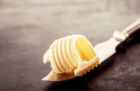 mantequilla: Cierre de la mantequilla en un cuchillo de pan relleno, coloca encima de una mesa de madera de la vendimia