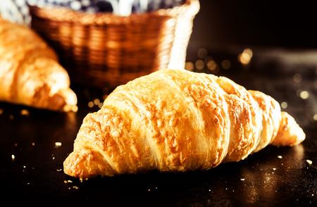 バターを食べるとテーブルの上にサクサクのおいしい自家製クロワッサン パンの準備完了間近します。 写真素材