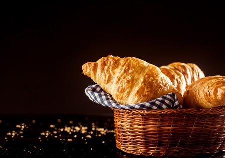暗い背景にテーブルの上に三日月形に新鮮なクロワッサン パンのバスケットを閉じます。