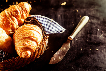 buttery: Close up Freshly Baked Buttery Croissant Bread on a Basket and a Cutting Knife on Top of the Table Stock Photo