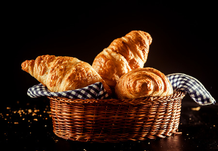 flaky: Close up Gourmet Buttery and Flaky Croissant Bread in Vienna Style on a Basket with Cloth on Top of a Table with Dark Background. Stock Photo