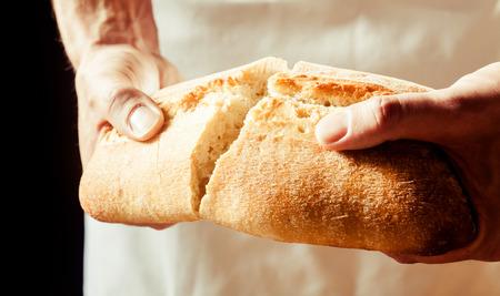 Hombre que rompe un pan crujiente recién horneado de pan blanco con las manos mientras se prepara para disfrutar de un aperitivo a mediodía, vista de cerca de las manos Foto de archivo