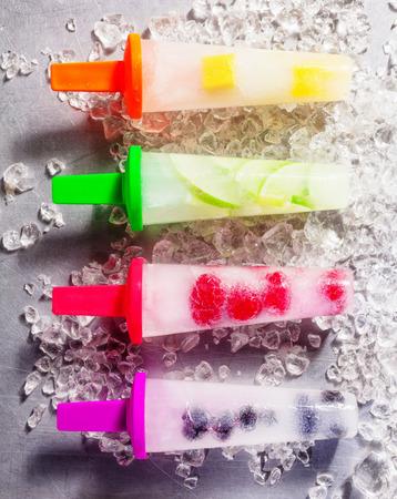 paletas de hielo: Cuatro paletas congeladas de frutas frescas con diferentes sabores naturales en los palillos de plástico de colores brillantes, alineados sobre hielo picado, de alto ángulo de close-up