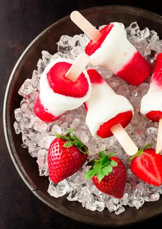 ice crushed: Lekker koud low-calorie dessert gemaakt van bevroren aardbeien yoghurt ijs stick met rauwe groenten op gemalen ijs in een ronde metalen kom, high-hoek close-up