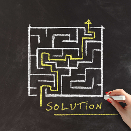 overcome: Solution or problem solving concept with a female hand drawing a maze or labyrinth on a blackboard with a yellow arrow marking the route through the puzzle Stock Photo