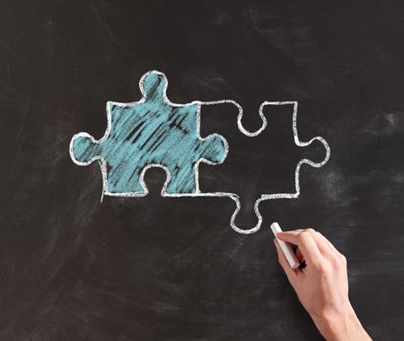 손 그리기 인테르는 블랙 보드에 분필로 다른 컬러 퍼즐 조각을 연결