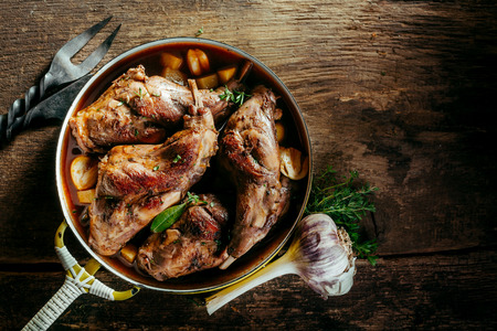 rustic food: High Angle View of Roasted Rabbit Haunches in Pan with Stewed Vegetables on Rustic Wooden Table Surface with Bulb of Garlic and Copy Space