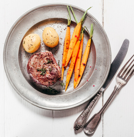 tin: High Angle View of Appetizing Roast Venison Steak Served on Metal Plate with Carrots and Potatoes Alongside Silver Cutlery on White Wooden Table Stock Photo