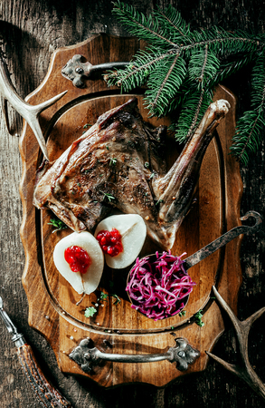 top down: High Angle View of Roasted Venison Haunch on Wooden Tray with Prepared Pears on Rustic Table with Evergreen Sprigs and Deer Antlers