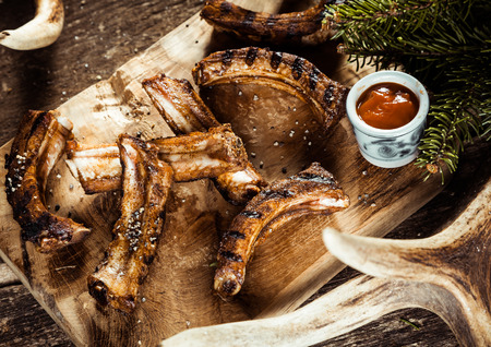 spare ribs: High Angle View of Grilled BBQ Venison Spare Ribs Served with Sauce on Wooden Board Accented by Evergreen Sprigs and Deer Antlers