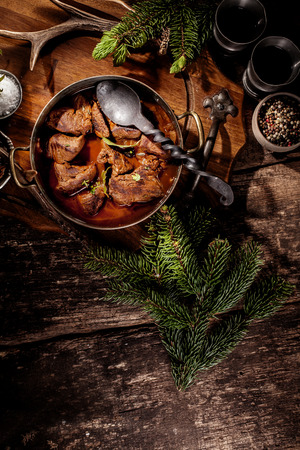 High Angle View of Venison Goulash Stew in Pot with Serving Spoon Surrounded by Evergreen Sprigs and Spices on Rustic Wooden Surface Stockfoto