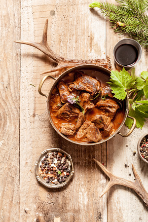 venado: Vista de ángulo alto de la carne de venado Goulash Stew en Olla con condimento en superficie de madera rodeado de astas de los ciervos y Puntillas árbol