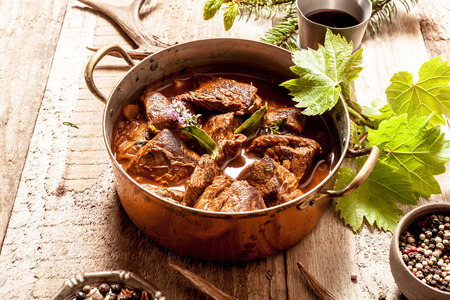 venison: Venison Goulash Stew in Copper Pot with Bowls of Seasoning on Wooden Surface Surrounded by Deer Antlers and Leaves