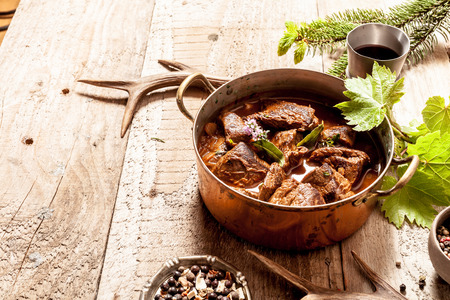 goulash: Venison Goulash Stew in Copper Pot with Bowls of Seasoning on Wooden Surface with Copy Space Surrounded by Deer Antlers and Leaves