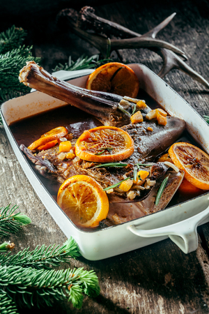 roasting pan: Roasted Venison Haunch in Roasting Pan Seasoned with Fresh Herbs and Orange Citrus Slices on Rustic Wooden Surface Surrounded by Evergreen Sprigs and Deer Antlers Stock Photo
